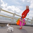 Young shopping woman whit dog ,sea background — Stock Photo