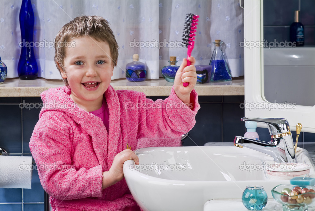 Little girl combing her hair with a brush in the bathroom — Stock Photo #10035268