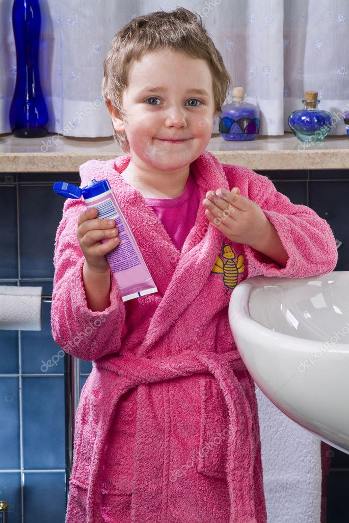 Little girl who puts the cream on your face in the bathroom — Stock Photo #10035480