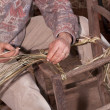 Carpenter weaves straw — Stock Photo