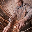 Stock Photo: Carpenter weaves rattan