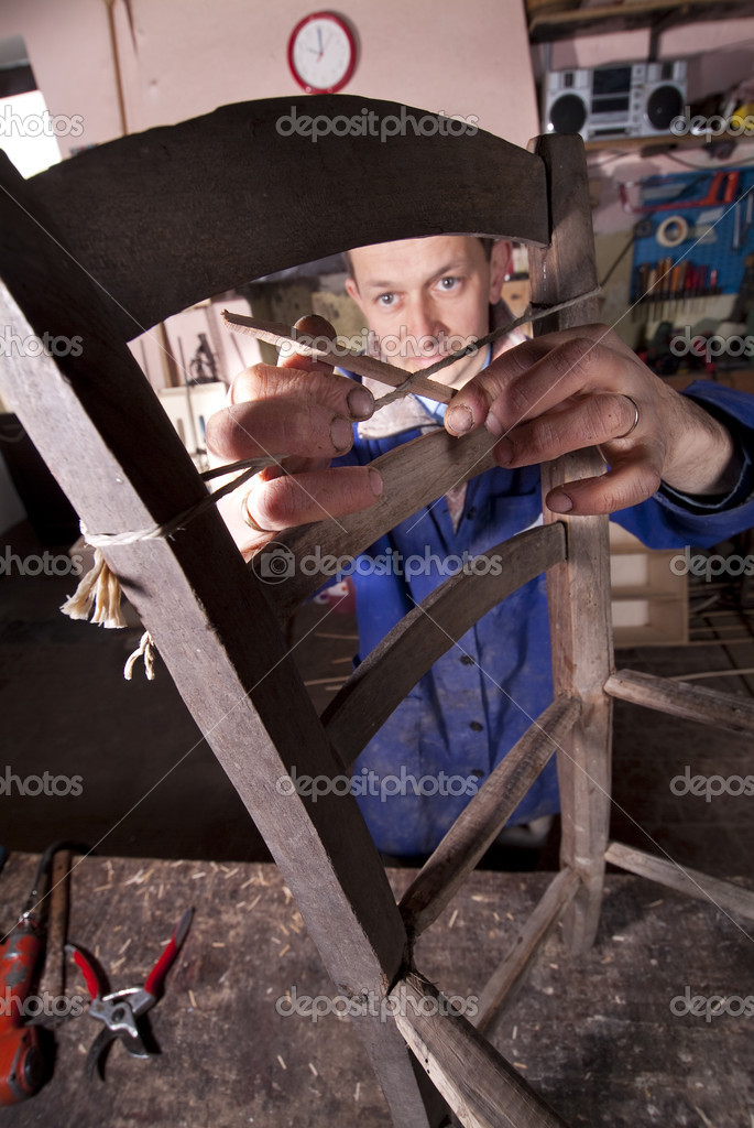 Carpenter repairing an old chair using old wood — Stock Photo #10464693