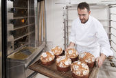 Pastry Chef, takes away the panettone baked of the oven — Stock Photo