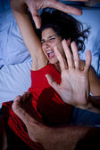 Battered woman on bed — Stock Photo