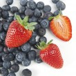 Blueberries and strawberries on a white background — Stock Photo