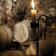 Old candle in a wine  barrel cellar - Stock Photo