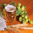 Hop and beer on wooden background — Stock Photo