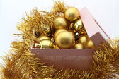 Golden new year's balls to box on white background — Stock Photo