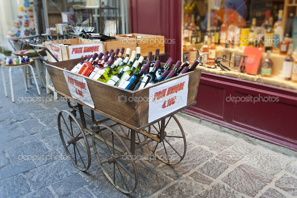 A cart of wine for sale in front of a wine and liquor shop in Uzes France — Stock Photo #10397052