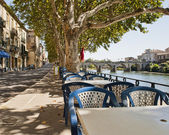 Tables along the river in Sommieres France — Stock Photo
