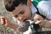 Niño beber agua de un grifo — Foto de Stock
