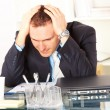Stressed businessman sitting at desk - Stock Photo