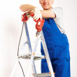 Man with drill standing on ladder - Stock Photo