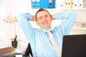 Happy businessman sitting — Stock Photo