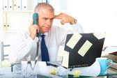 Stressed businessman sitting at desk — Stock Photo