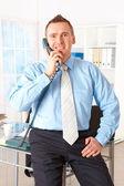 Felice imprenditore appoggiato sulla scrivania con telefono — Foto Stock