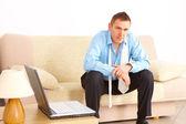 Tired businessman sitting on sofa — Stock Photo