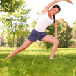 Stock Photo: Young woman doing stretching exercise on green grass
