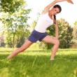 Young woman doing stretching exercise on green grass — Stock Photo
