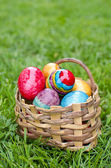 Easter eggs in basket on green grass — Stock Photo