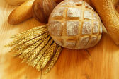 Assorted bread on wooden table with raw wheat — Stock Photo