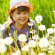 Smiling girl in a field of dandelions — Stock Photo