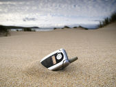 Forgotten mobile phone on the beach — Stock Photo