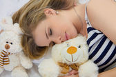 Beautiful girl sleeping with toys. — Stock Photo