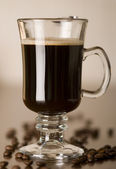 Black coffee in the glass with coffee beans — Stock Photo