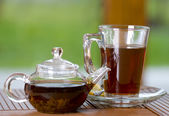 Glass of tea with teapot — Stock Photo