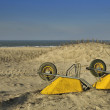 Stock Photo: 2 Yellow wheelbarrows in dunes