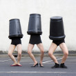 Stock Photo: Three trash cans cover three women heads