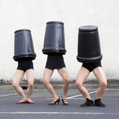 Three trash cans cover three women heads — Stock Photo