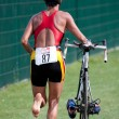 Stock Photo: Triathlete pushing his bike