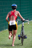 Triathlete pushing his bike — Stock Photo