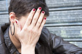 Woman hiding her face behind her right hand — Stock Photo