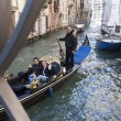 Gondola with a happy couple in a narrow canal — Stock Photo