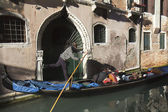Gondolier driving a gondola in a narrow canal — Stock Photo