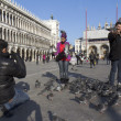Tourists are having fun with the pigeons — Stock Photo