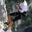 Stock Photo: Descent of a young female rock climber