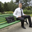 Stock Photo: Businessmsitting on bench.