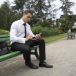 Stock Photo: Young business msitting on bench