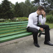 Young businessman sitting on a bench. — Stock Photo