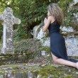 Young woman  kneeling in front of a stone cross. — Stock Photo