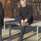 Elderly man sitting on a bench and tying shoes, — Foto de Stock