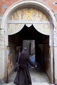 Clergy man walking under a door — Stock Photo
