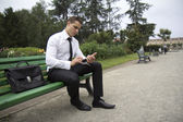 Young business man sitting on a bench — Stock Photo