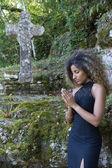 Femme priant à côté d'une croix de pierre. — Photo