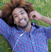 Young african american male lying in grass — Stock Photo