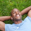African American man lying in grass listening to music - Stock Photo